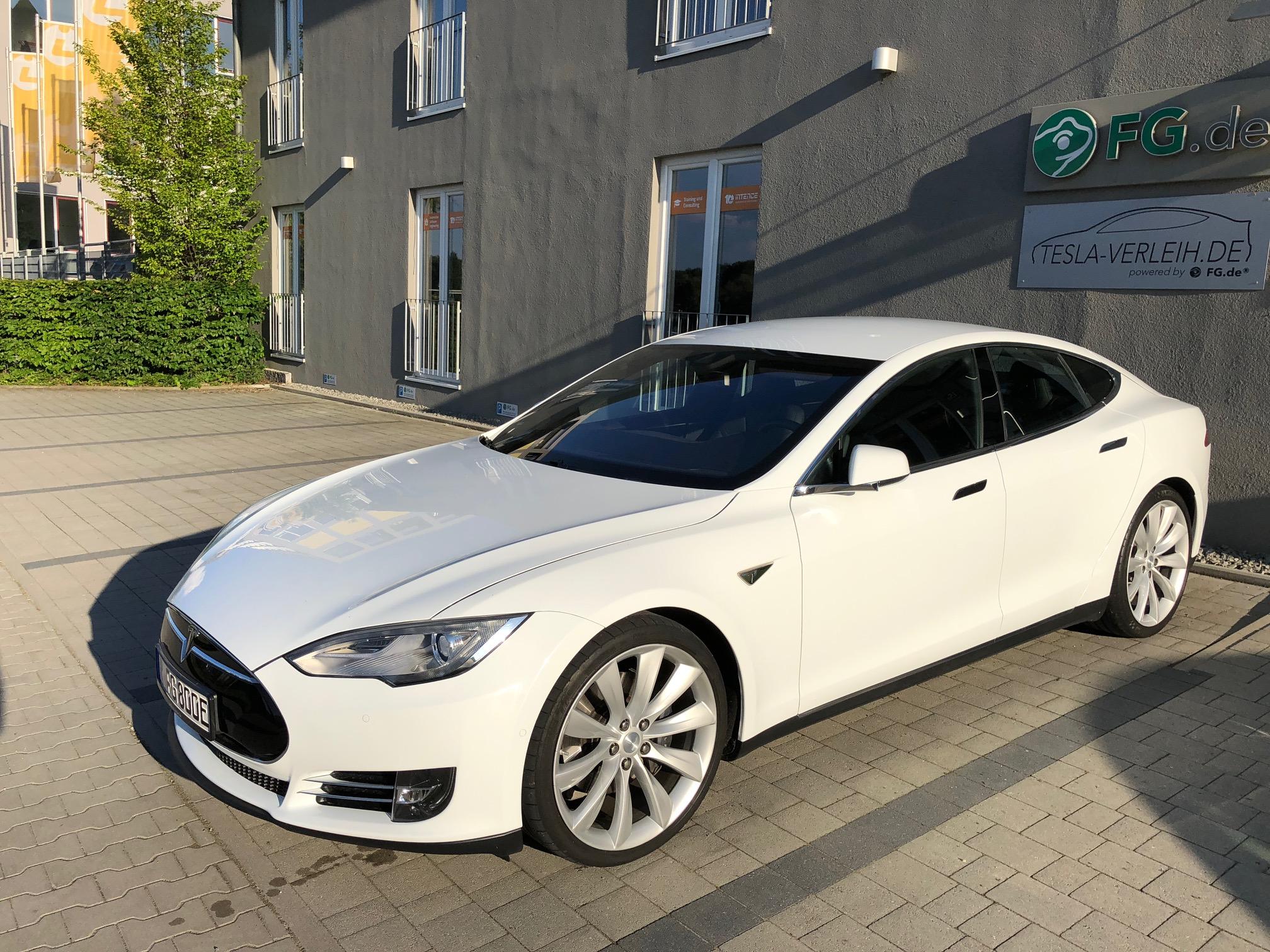 Ein weißer Tesla steht auf einem Parkplatz vor einem Firmengebäude